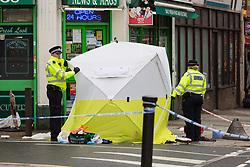 A cordon is in place as abandoned first aid equipment lies next to a tent covering the body of a man in his 30s who was stabbed outside an off licence in the early hours of Sunday February 10th on Lordship Lane, East Dulwich in London. London, February 10 2019.
