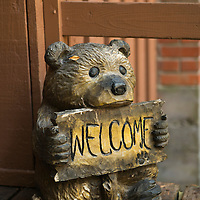 A wooden bear holding a welcome sign. Heaven's Gate River Cottages are vacation rentals located along the McKenzie River near Vida, Oregon.