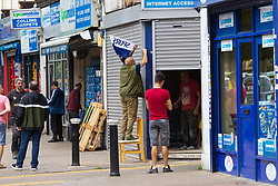 A builder affixes a Spurs flag to a shopfront ahead of Tottenham's Champions League final with Liverpool to be played at Atletico Madrid's Wanda Metropolitano Stadium in Madrid. Tottenham, London, May 31 2019.