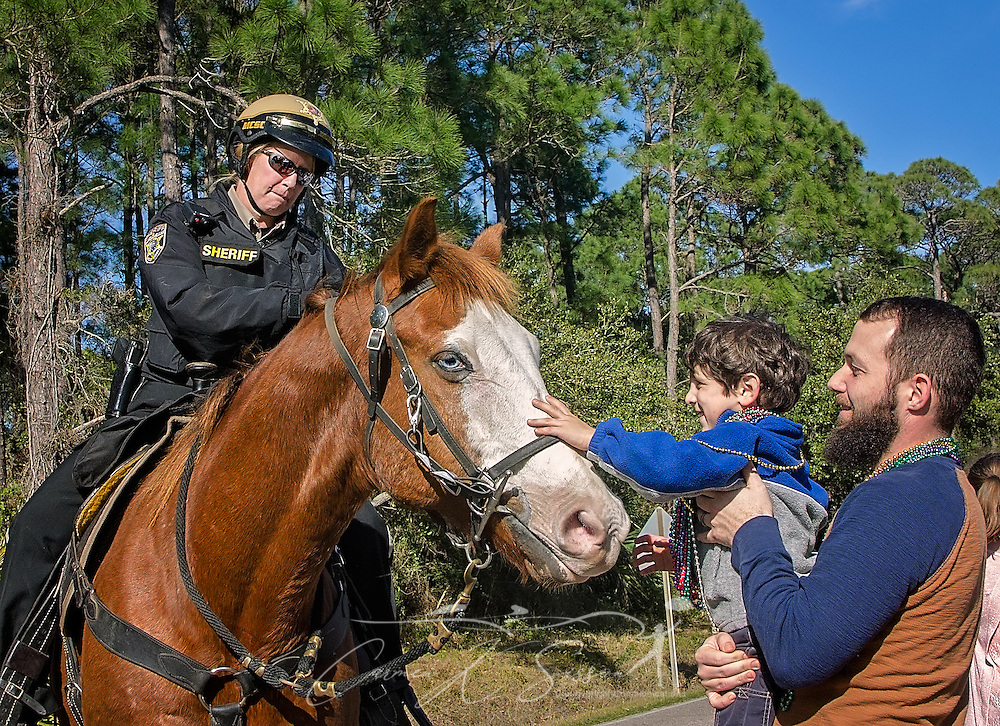 A Mobile County police deputy stops to allow Shawn Irby, 4 to pet her horse as they make their way down Bienville Boulevard in Dauphin Island's first People's Parade during Mardi Gras, Feb. 4, 2017, in Dauphin Island, Alabama. French settlers held the first Mardi Gras in 1703, making Mobile's celebration the oldest Mardi Gras in the United States. The first parade of the season is traditionally held on Dauphin Island and draws thousands. (Photo by Carmen K. Sisson/Cloudybright)