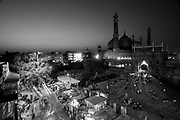 "An elevated view of the Jama Masjid mosque at dusk in Old Delhi on the 5th October 2011<br /> <br /> The Masjid-i Jahan-Namaa (Persian: the 'World-reflecting Mosque'), commonly known as the Jama Masjid of Delhi, is the principal mosque of Old Delhi in India. Commissioned by the Mughal Emperor Shah Jahan, builder of the Taj Mahal, and completed in the year 1656 AD, it is one of the largest and best-known mosques in India. It lies at the origin of a very busy central street of Old Delhi, Chandni Chowk.<br /> The later name, Jaama Masjid, is a reference to the weekly Friday noon congregation prayers of Muslims, which are usually done at a mosque, the ""congregational mosque"" or ""jaama masjid"". The courtyard of the mosque can hold up to twenty-five thousand worshipers. The mosque also houses several relics in a closet in the north gate, including a copy of the Qur'an written on deer skin.<br /> <br /> The mosque was the result of the efforts of over 5,000 workers, over a period of six years. The cost incurred on the construction in those times was 10 lakh (1 million) Rupees. Shah Jahan built several important mosques in Delhi, Agra, Ajmer and Lahore. The Jama Masjid's floorplan is very similar to the Jama Masjid at Agra, but the Jama Masjid is the bigger and more imposing of the two. Its majesty is further enhanced because of the high ground that he selected for building this mosque. The architecture and design of the Badshahi Masjid of Lahore built by Shah Jahan's son Aurangzeb in 1673 is closely related to the Jama Masjid in Delhi.<br /> <br /> PHOTOGRAPH BY AND COPYRIGHT OF SIMON DE TREY-WHITE"
