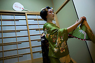 Miehina, a 20 year old maiko ( an apprentice geisha) from the Miyagawacho district of Kyoto, performs a dance for her evening clients in a small room adjoining the bar where they sit, in the tea house where she lives and works, Kyoto, Japan, Sunday, May 18th 2008.