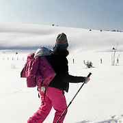 A woman walking on snowshoes