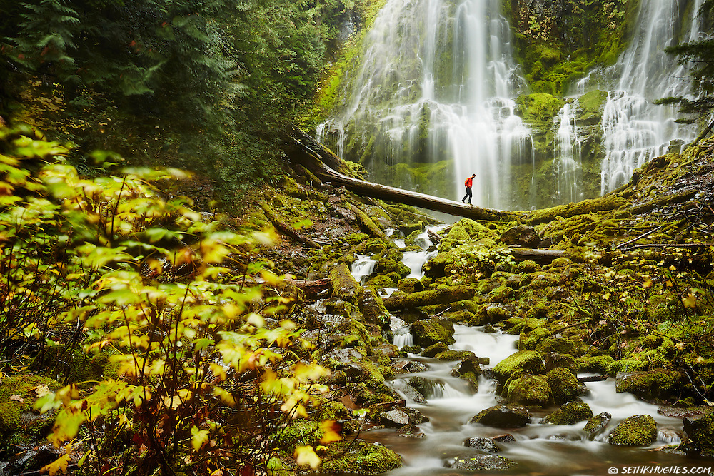 A hiker crosses the stream below Proxy Falls on McKenzie Pass in the Cascade Mountains of Oregon.