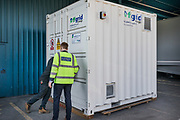 London, England, UK, September 6 2018 - At UPS Central London site, employees of UPS and UK Power Networks Services close the door of the box containing onsite energy storage batteries.<br /> A UPS led consortium with UK Power Networks Services and Cross River Partnership has deployed a new charging technology in London that overcomes the challenge of simultaneously recharging an entire fleet of electric vehicles (EVs) without the need for the expensive upgrade to the power supply grid. The technology, based on the use of onsite energy storage batteries, is now used to provide extra energy needed during peak hours, but it should also allow to increase the number of EVs operating from UPS central London site from the current limit of 65 to all 170 trucks based there.