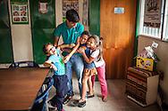 Niñas del Barrio San Miguel de La Vega abrazan a uno de los jóvenes del programa Casa Universitaria Padre Alberto Hurtado (CUPAH) durante las actividades organizadas en el barrio. Caracas, Nov. 08, 2013 (Foto/Ivan Gonzalez)