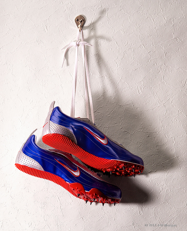 Nike track shoes hanging on a wall hook.