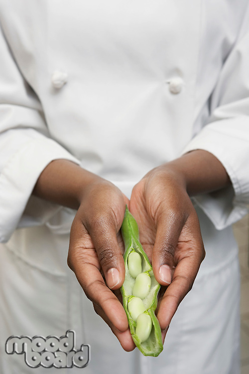 Female chef holding vegetables mid section