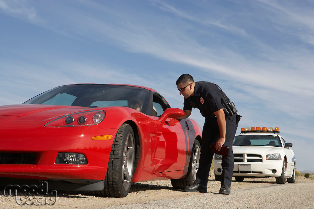 Traffic cop talking with driver of red sports car