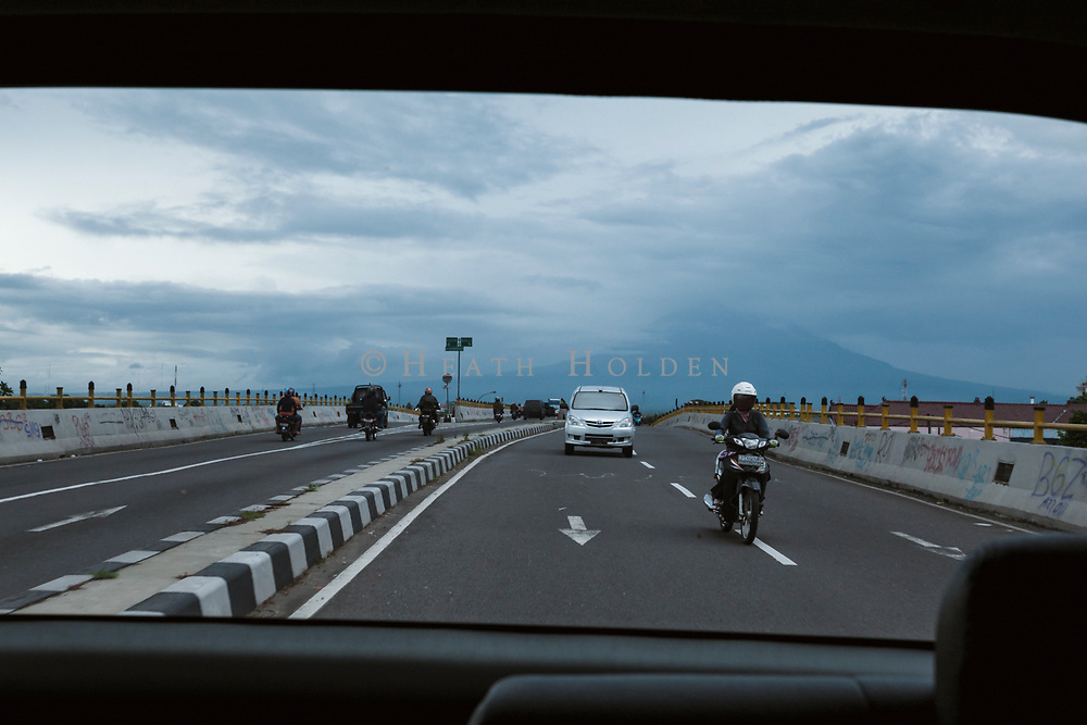 A cloud covered Mt Merapi can be seen through the back of a taxi driving through Yogyakarta, Java.