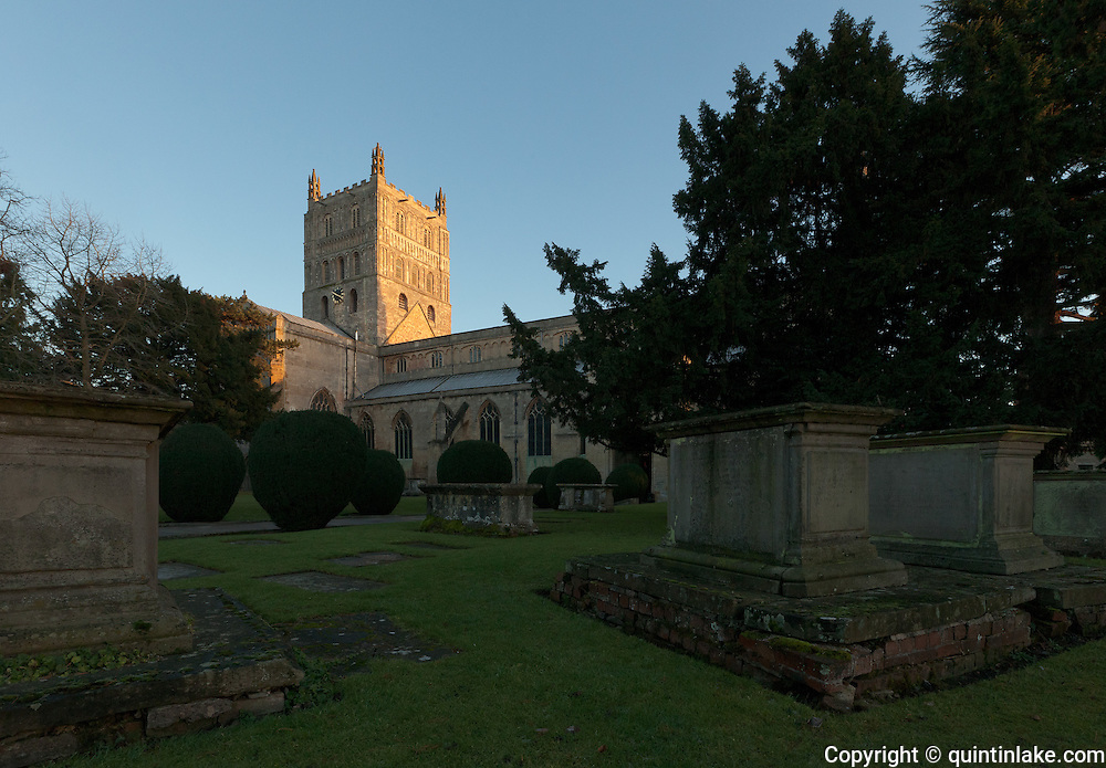 Exterior of north and west facing facade of Tewkesbury Abbey at sunset ith gravestones