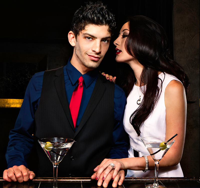 Faye Viviana whispering into Joseph Anderson's ear at a bar