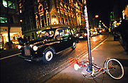 a black cab drives past a bicycle that has fallen over, London, U.K, 1990s.