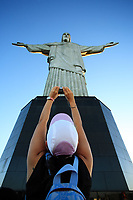 tourist taking a picture of the corcovado christ redeemer in rio de janeiro brazil