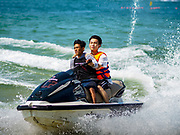 "13 FEBRUARY 2019 - SIHANOUKVILLE, CAMBODIA: Chinese tourists on Ocherteal Beach in Sihanoukville ride on personal watercraft that are being steered by Cambodian workers. There are about 80 Chinese casinos and resort hotels open in Sihanoukville and dozens more under construction. The casinos are changing the city, once a sleepy port on Southeast Asia's ""backpacker trail"" into a booming city. The change is coming with a cost though. Many Cambodian residents of Sihanoukville  have lost their homes to make way for the casinos and the jobs are going to Chinese workers, brought in to build casinos and work in the casinos.      PHOTO BY JACK KURTZ"