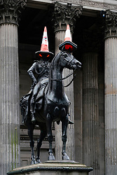 Statue of Duke of Wellington wearing his usual traffic cones in Royal Exchange Square in the Merchant City of Glasgow, Scotland, UK