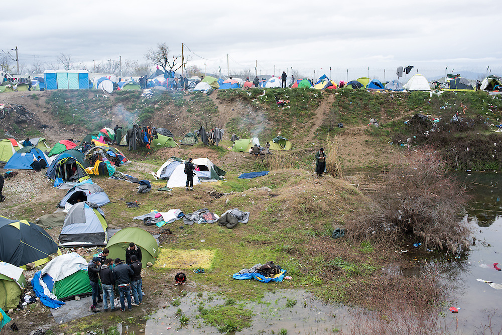 View of the Idomeni camp where it has been raining non stop for the last few days. The fence build by the FYR Macedonian Police is visible at the back. Transit camp of Idomeni, Greece. <br /> <br /> Thousands of refugees are stranded in Idomeni unable to cross the border. The facilities are stretched to the limit and the conditions are appalling.