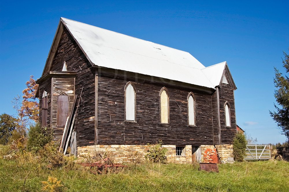 An abandoned country church in weathered wood siding without stained glass windows and vestibule in rear.
