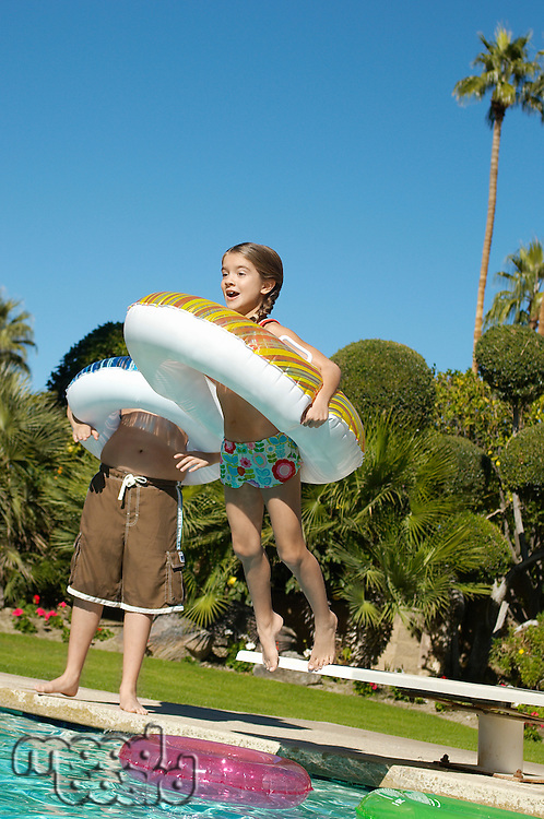 Girl jumping into swimming pool with inflatable raft