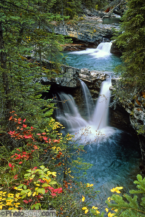 Waterfalls and fall leaf colors in Johnston Canyon, Banff National Park, Alberta, CANADA. This is part of the big Canadian Rocky Mountain Parks World Heritage Site declared by UNESCO in 1984. Image was licensed by Tennessee Valley Bottling Company, Alabama for use as marketing screening for a water bottle label.