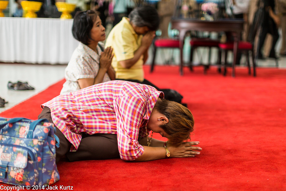 09 OCTOBER 2014 - BANGKOK, THAILAND:  A woman prays for Bhumibol Adulyadej, the King of Thailand in the lobby of Siriraj Hospital. The King has been hospitalized at Siriraj Hospital since Oct. 4 and underwent emergency gall bladder removal surgery Oct. 5. The King is also known as Rama IX, because he is the ninth monarch of the Chakri Dynasty. He has reigned since June 9, 1946 and is the world's longest-serving current head of state and the longest-reigning monarch in Thai history, serving for more than 68 years. He is revered by the Thai people and anytime he goes into the hospital thousands of people come to the hospital to sign get well cards.  PHOTO BY JACK KURTZ