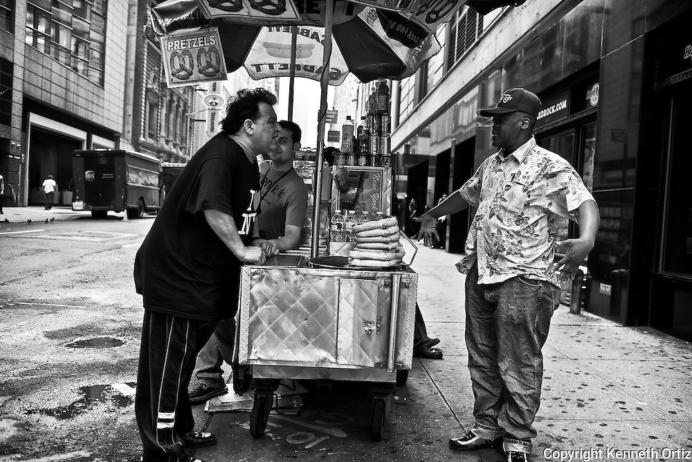 A hot dog vendor and a customer having a discussion in Times Square, New York City.