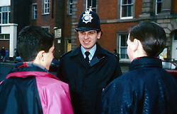 Community police officer standing in street talking to two young boys,
