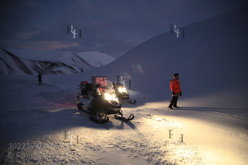 Russian snowmobile guide surveys frozen landscape halfway between Longyearbyen and Barentsburg in January; Svalbard, Norway.