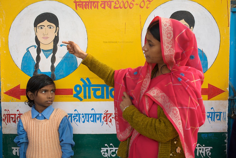 Smarika, a teacher at the Khanjadipur primary school and anganwadi centre, demonstrates good hygiene practice to pupils in her care. The school handwashing area and toilet are adorned with colourful paintings and are an example of the kind of attractive facitilty encouraged by UNICEF. The anganwadi centre boasts a small baby-friendy latrine...UNICEF and the Uttar Pradesh Government, have identified 36 model Gram Panchayats (local-level village administration) in Mirzapur District. The promotion of good sanitation and hygiene practices in these Gram Panchayats allows them to serve as examples for the remaining areas of the district to emulate. The promotion of hygiene and sanitation includes the construction and painting of school toilet blocks, the construction of individual toilets in households, the digging of garbage pits, recycling waste water and encouraging personal hygiene awareness. ..Only 32 percent of those living in Uttar Pradesh, India's largest state, have access to a toilet. Uttar Pradesh faces many challenges in it's efforts to address this deficiency. UNICEF supports the Uttar Pradesh government's sanitation and hygiene project at both the state and district levels. UNICEF is working to increase the capacity of all of those involved in the sanitation and hygiene project from state-level administrators through to Panchayati Raj (local-level administration) officers and influential individuals, including teachers, who live among rural communities. UNICEF has prioritised the need to communicate the importance of good sanitation and hygiene practice to these communities. The Uttar Pradesh government and UNICEF have focussed their campaign on eight districts (including Mirzapur) with the intention that these serve as models for the remaining 62 districts of the state. UNICEF have identified areas of shortcoming within the government program and proposed solutions. These solutions include the proper training of masons, the provision of rural pans (toilet b