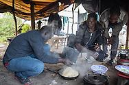Calais, Pas-de-Calais, France - 17.10.2016    <br />  <br /> Eritrean refugees cook porridge for dinner. &rdquo;Jungle&quot; refugee camp on the outskirts of the French city of Calais. Many thousands of migrants and refugees are waiting in some cases for years in the port city in the hope of being able to cross the English Channel to Britain. French authorities announced that they will shortly evict the camp where currently up to up to 10,000 people live.<br /> <br /> Eritreische Fluechtlinge kochen Haferbrei zum Abendessen. &rdquo;Jungle&rdquo; Fluechtlingscamp am Rande der franzoesischen Stadt Calais. Viele tausend Migranten und Fluechtlinge harren teilweise seit Jahren in der Hafenstadt aus in der Hoffnung den Aermelkanal nach Gro&szlig;britannien ueberqueren zu koennen. Die franzoesischen Behoerden kuendigten an, dass sie das Camp, indem derzeit bis zu bis zu 10.000 Menschen leben K&uuml;rze raeumen werden. <br /> <br /> Photo: Bjoern Kietzmann
