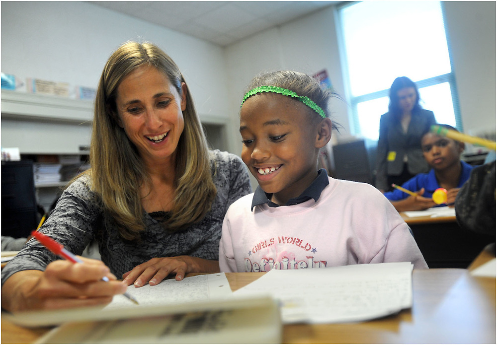 Fourth-grade teacher Tracie Tkacik helps Daysia Coles on a writing assignment.  Bass Elementary is also the only school in the area that runs on a year-round schedule.  Tkacik is a fan of the extended year schedule and intercessions, which allow for quick reviews of topics.
