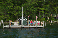 Anna, Julie and Katelyn Herrmann with other island residents participate in the long standing tradition of jumping from the dock pilings at Jolly Island as the MV Sophie C departs on her mail route on Lake Winnipesaukee.  (Karen Bobotas/for the Laconia Daily Sun)