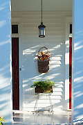 Hanging basket floral display on stoop of stylish clapboard house in Natchez, Mississippi, USA