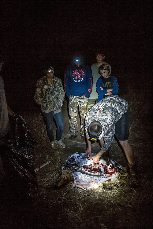The trackers are shown how to properly field dress the deer shot by Karina Jacany.