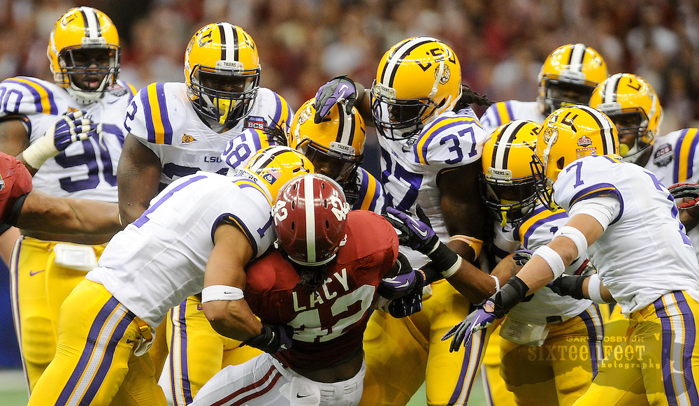 Daily Photo by Gary Cosby Jr.    ..Eddie Lacy is wrapped up and tackled by a swarm of LSU defenders but only after gaining enough for a first down during the second half of the BCS National Championship Game between Alabama and LSU in the Superdome Monday night...................................