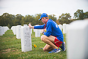 Seamus Donahue, 18, places his Marine Corps Marathon finisher's medal on the grave of his father, Maj. Michael Donahue, at Arlington National Cemetery on Oct. 25, 2015. Seamus ran the marathon in honor of his father who was killed in Kabul, Afghanistan on Sept. 16, 2014. Seamus runs with wear blue: run to remember, a national non-profit that builds running communities that honor the service and sacrifice of the American military, while providing families of fallen service members training and support for endurance racing as a means to heal and thrive in the aftermath of ultimate sacrifice.
