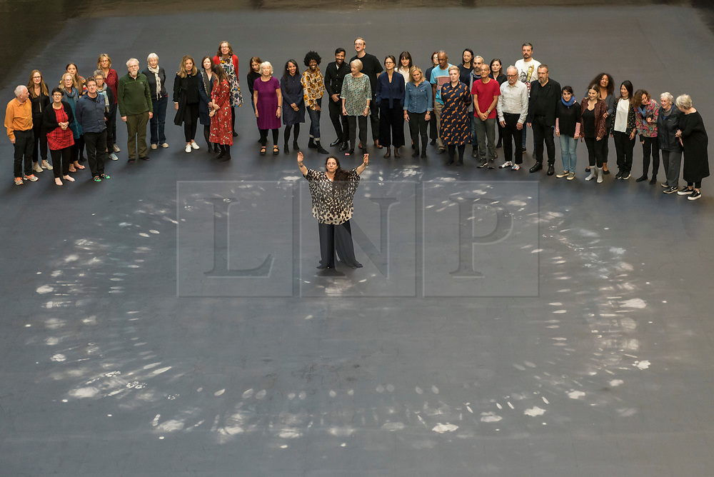 """© Licensed to London News Pictures. 01/10/2018. LONDON, UK. Tania Bruguera (front) stands with volunteers after leaving body impressions on the heat-sensitive floor. Unveiling of the this year's Hyundai Commission by Cuban artist and activist Tania Bruguera at Tate Modern.  The work is called """"an ever-increasing figure"""", which represents the scale of mass migration and the risks involved.  Visitors are invited to interact with the work which comprises a heat-sensitive floor, which includes a portrait of a person's face beneath, combined with low frequency sounds.  The work is on display 2 October to 24 February 2019..  Photo credit: Stephen Chung/LNP"""