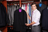 Portrait of confident man showing new suits in store
