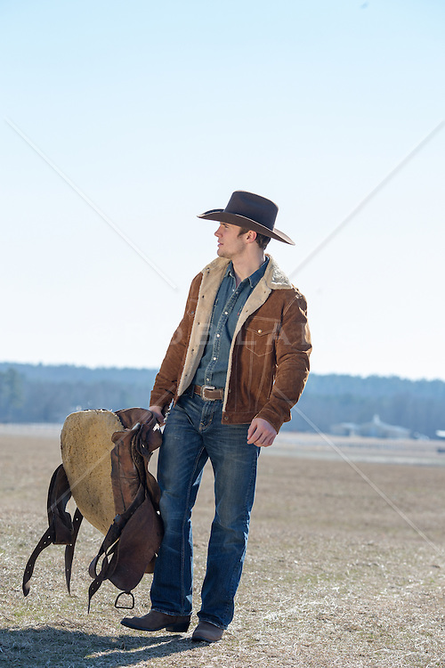 cowboy walking on a ranch with a saddle in his hand