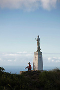 A man sits beneath the statue atop Mt. Tapochau in Saipan on 22 Feb 2011. .Photographer: Robert Gilhooly