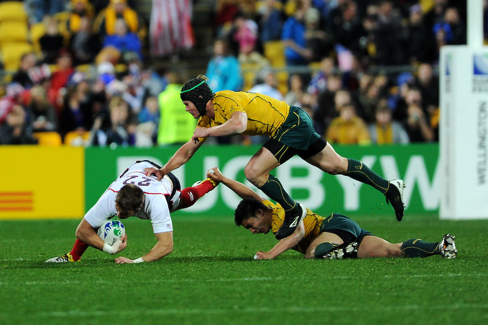 Chris Wyles gets tackled while Anthony Faingaa is knocked unconcious during the Pool C, Australia v USA match at the IRB Rugby World Cup 2011. Wellington Regional Stadium, Wellington. Friday 23 September 2011...Photo: Mark Tantrum/photosport.co.nz..