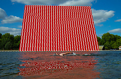 A swimmer at the Serpentine's lido swims past artist Christo's 20m high installation on The Serpentine made from over 7000 barrels, titled The Mastaba, which will be on the Serpentine until 23 September 2018. The Installation is comprised of 7,506 horizontally stacked barrels. It is 20m high, 30m wide and 40m long. Hyde Park, London, June 18 2018.