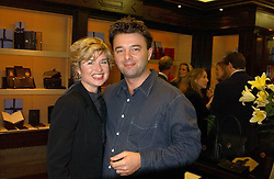 Left to right, ISSY VAN RANDWYCK and her husband MR EDWARD HALL son of Peter Hall at a party to celebrate the launch of The Monneypenny Diaries at Smythson, 40 New Bond Street, London W1 on 4th October 2005.<br />