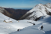 Man hiking in snowy mountain landscape towads isolated cabin near the Col de Pause, in winter, Ariege Pyrenees, France.