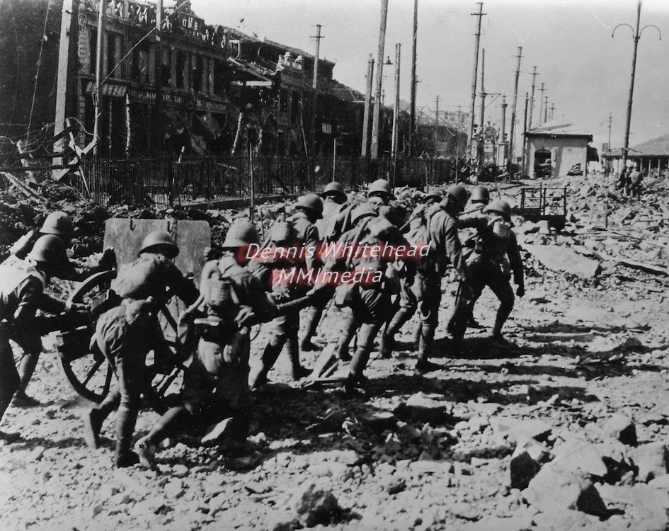 November 14, 1937 - Shanghai - As the Chinese withdraw from Shanghai on October 27, 1937, Japanese bluejackets hastily move one of their field artillery pieces into posiiton among the ruins of Chapei so that they can blast the stubbornly fighting Chinese from a position that is holding up their advance.
