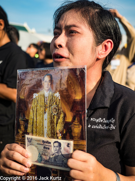 22 NOVEMBER 2016 - BANGKOK, THAILAND:  A woman weeps while singing the royal anthem to honor Bhumibol Adulyadej, the Late King of Thailand, at Sanam Luang Tuesday. Hundreds of thousands of Thais gathered across Thailand Tuesday to swear allegiance to the Chakri Dynasty in a ceremony called Ruam Phalang Haeng Kwam Phakdi (the United Force of Allegiance). At Sanam Luang, the Royal Parade Ground, and location of most of the mourning ceremonies for the late King, people paused to honor His Majesty by singing the Thai national anthem and the royal anthem.      PHOTO BY JACK KURTZ