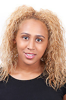 Portrait of happy young mixed race woman with blond curly hair against white background