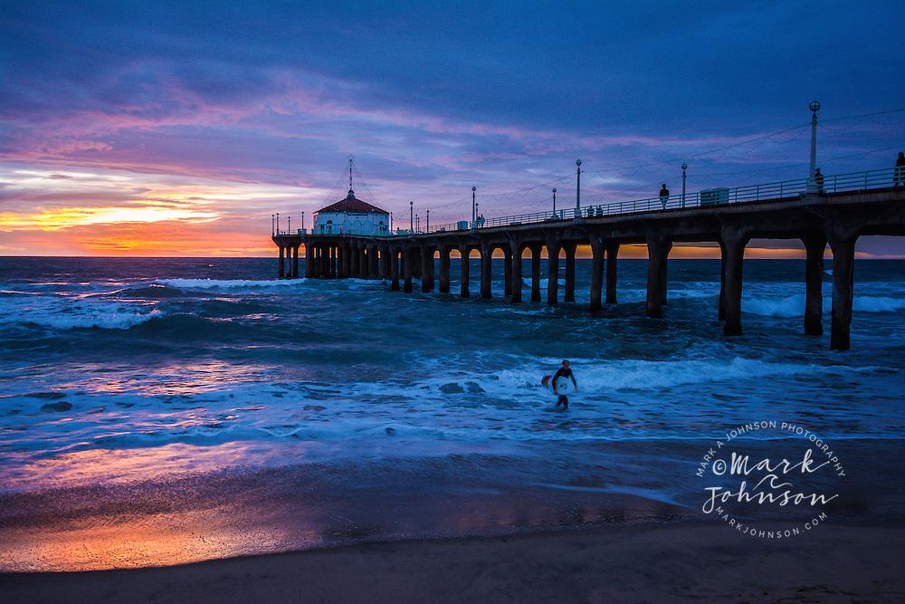 Surfer exiting the ocean after surfing off the Manhattan Beach Pier, Manhattan Beach, Los Angeles, California, USA