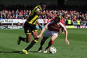 Barnsley defender George Williams and Burton Albion forward Lucas Akins come challenge for the ball during the Sky Bet League 1 match between Burton Albion and Barnsley at the Pirelli Stadium, Burton upon Trent, England on 16 April 2016. Photo by Aaron  Lupton.