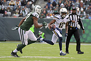 Dec 24, 2017; East Rutherford, NJ, USA; Los Angeles Chargers wide receiver Travis Benjamin (12) carries the ball as New York Jets outside linebacker David Bass (47) defends during an NFL football game at MetLife Stadium. The Chargers defeated the Jets 14-7.